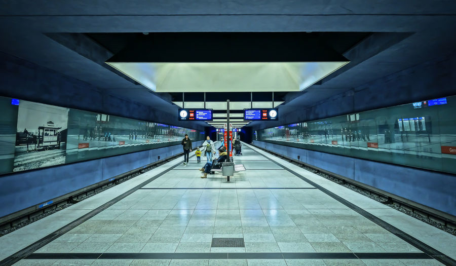 symmetry on Station ... Architecture Reflection Motion Real People Modern Street Photography Blue Travel Ceiling Airport Symmetry Illuminated Transportation Direction Public Transportation Perspective Indoors  Engineering Composition Ubahnhof Urban Geometry Leading Hdr_Collection U-Bahnhof Moving Walkway  Architecture_collection Flooring Blurred Motion Railroad Station The Way Forward Built Structure Incidental People Glass - Material Diminishing Perspective Railroad Station Platform Global Photographer Works Exhibition Mode Of Transportation The Graphic City Mobility In Mega Cities Krull&Krull Architecture The Art Of Street Photography