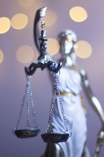 Close-up of lady justice against illuminated lights