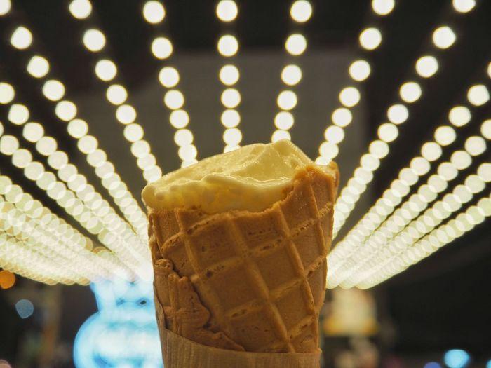 Close-up of ice cream against illuminated lighting equipment