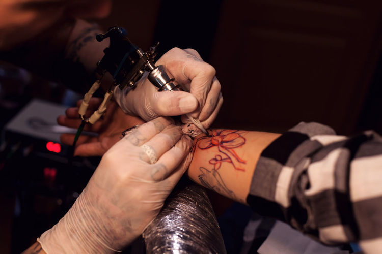 Tattoo artist is inserting ink into the skin using sterilized nitrile gloves and tattoo machine Finger Tattooing Art And Craft Arts Culture And Entertainment Lifestyles Close-up Men People Skill  Two People Focus On Foreground Tattoo Creativity Artist Indoors  Occupation Holding Human Body Part Real People Hand Human Hand Indoors  Skill  Women Customer  Working