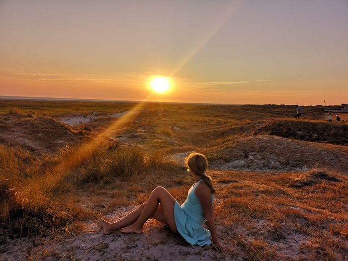 Side view of woman sitting on field against sky during sunset