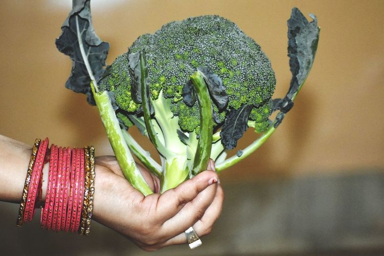Close-up of woman holding broccoli