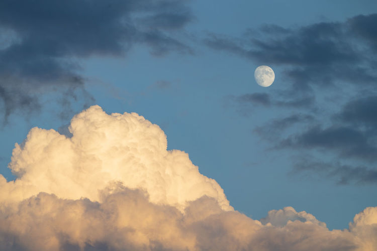 The photo shows a dramatically cloud formation with the moon in the sunset