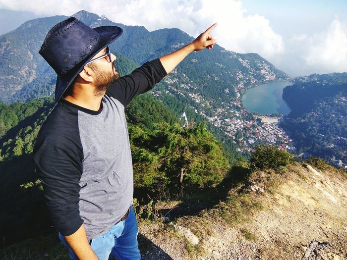 Man Gesturing While Standing On Mountain