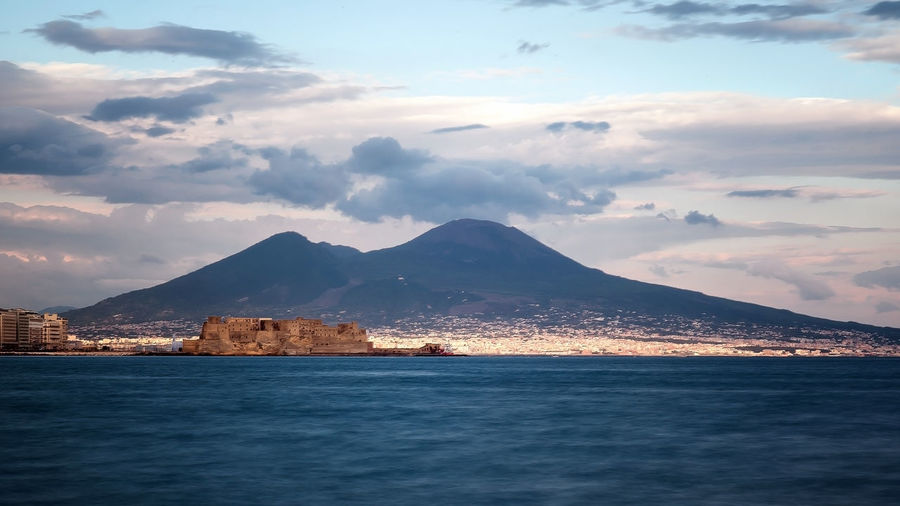 Mid distance view of castel dellovo by sea with mountains in background against cloudy sky