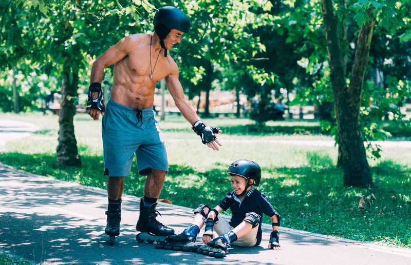 Shirtless grandfather giving hand to grandson fallen on footpath while skating in park