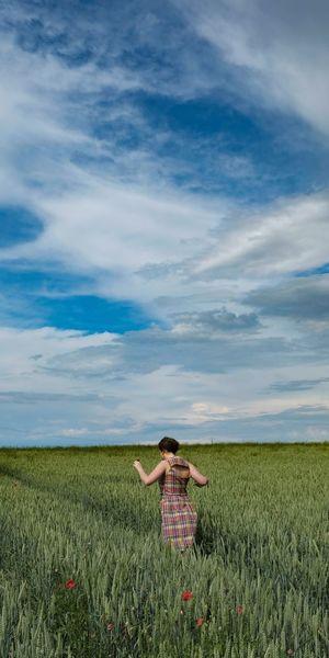 Woman walking on field against cloudy sky