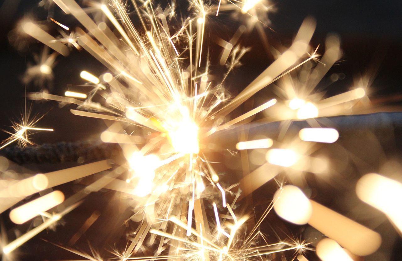 Close-up of lit sparkler at night