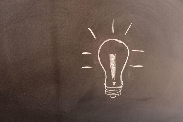 Close-up of illuminated light bulb on wall