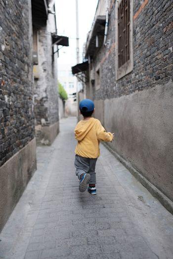 Rear view of boy walking on footpath amidst buildings