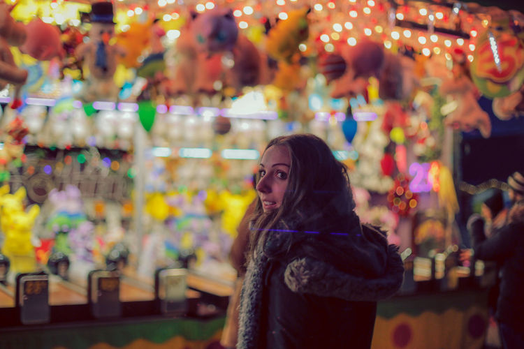 Side view of young woman looking away while standing in market at night