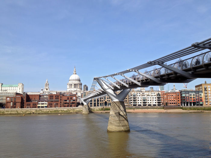 Millennium bridge over thames river by st paul cathedral against sky