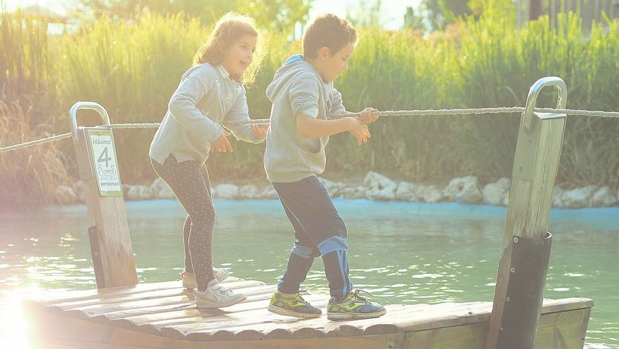 Full length of children playing on water