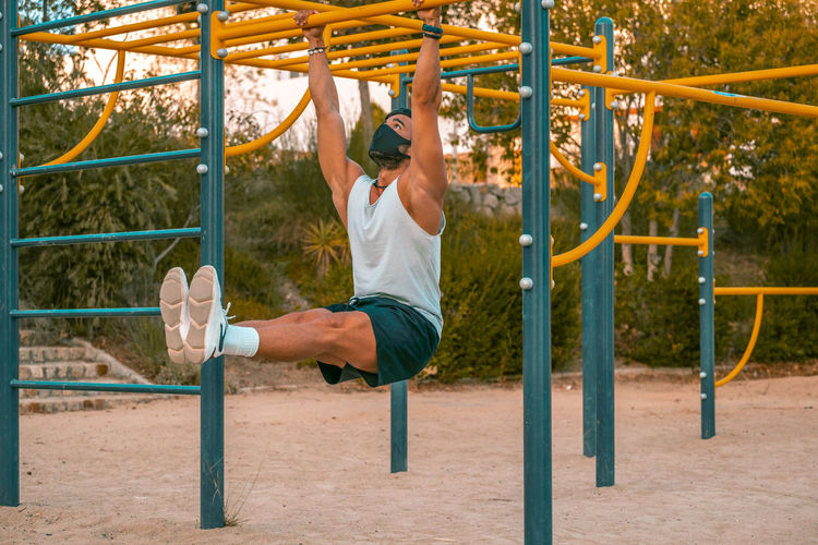 Full length of man wearing mask exercising at park