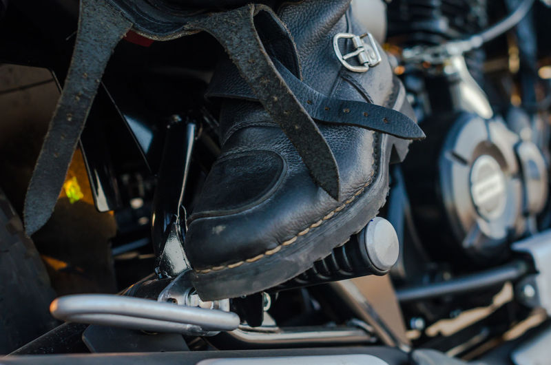 Low section of biker sitting on motorcycle