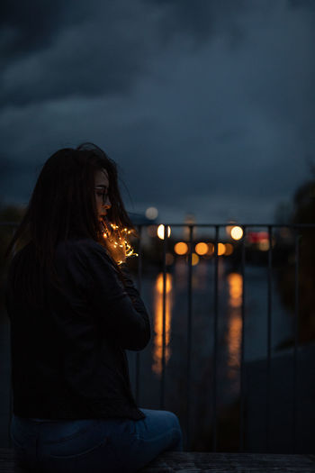 Woman Sitting With Illuminated String Lights On Railing Against River At Night