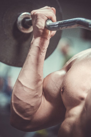 Close-Up Of Shirtless Muscular Man Lifting Barbell In Gym
