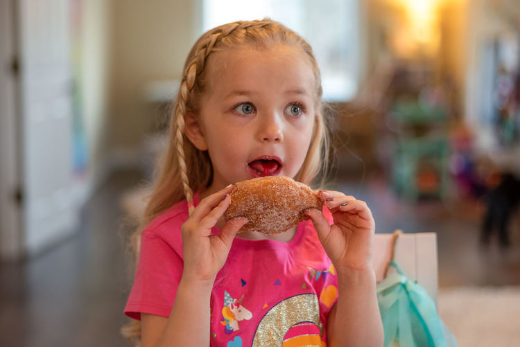 Portrait of girl eating food at home