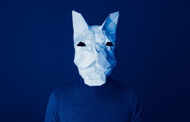 Person wearing french bulldog origami paper mask against blue background