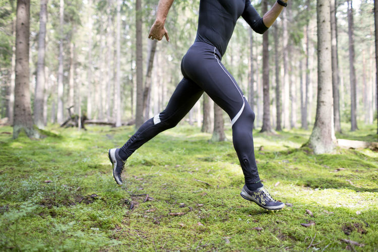 Low section of man running on road in forest