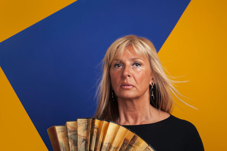 Close-Up Portrait Of Woman With Hand Fan Against Colored Background