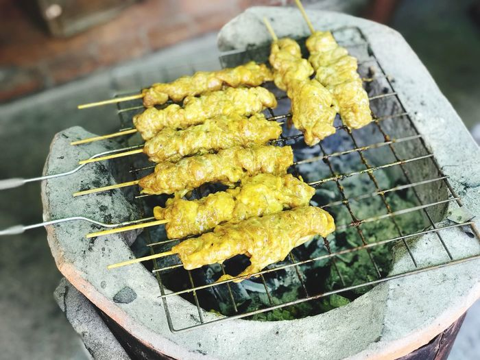 Chicken satay for appetizer being grilled on the rack. Thai Food Chicken Satay For Appetizer Food And Drink Freshness Day Food Outdoors Yellow Focus On Foreground Nature Close-up Grilled Preparation  High Angle View Metal Grate Healthy Eating No People