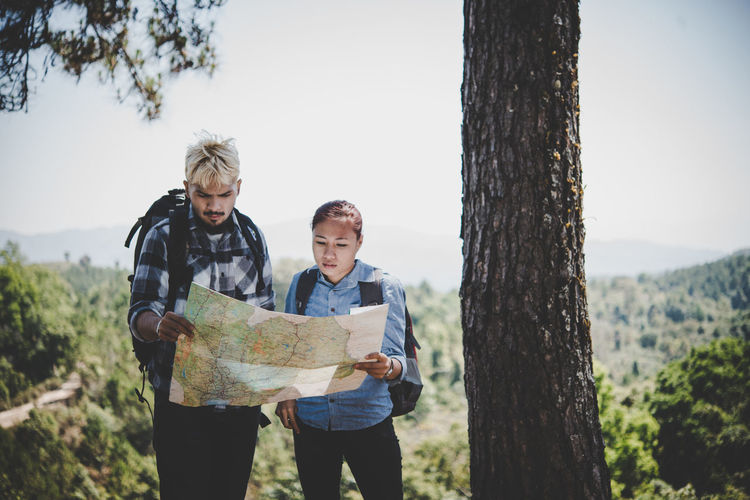 Man And Woman Reading Map At Forest