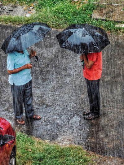 Rear view of man with umbrella during rainy season