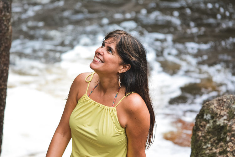 Cheerful Mature Woman Looking Up While Standing Outdoors