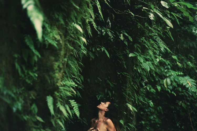 Sensuous shirtless woman against trees