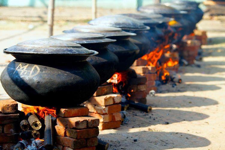 Food being cooked in containers on wood burning stoves