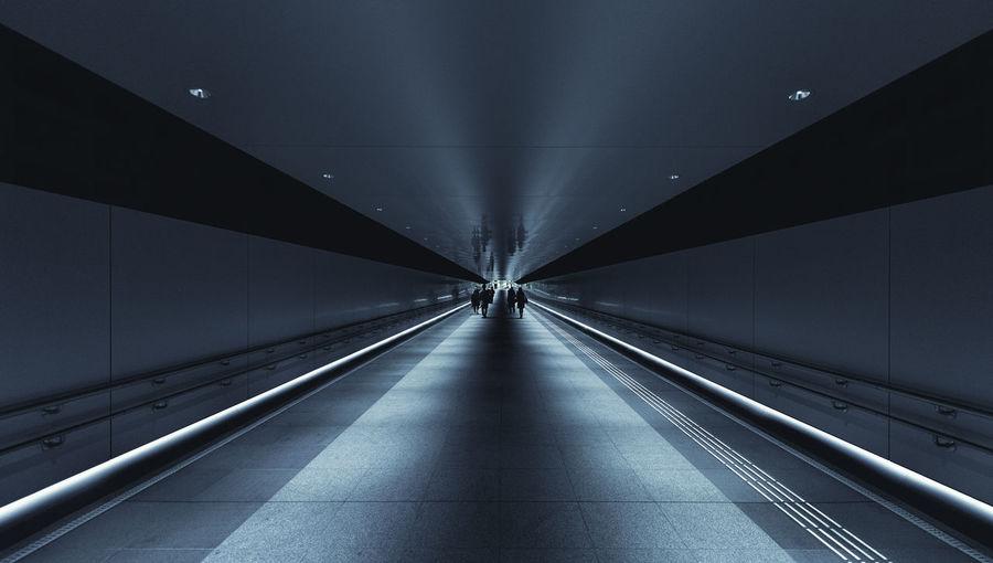 People walking in illuminated subway station platform
