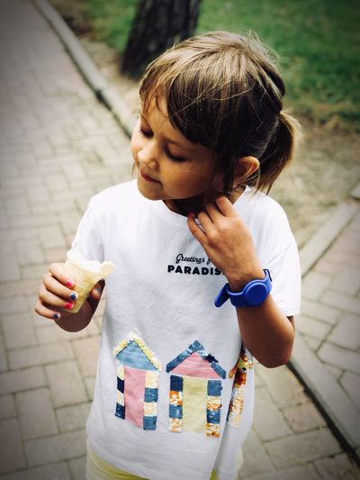 Cute girl holding ice cream standing on footpath