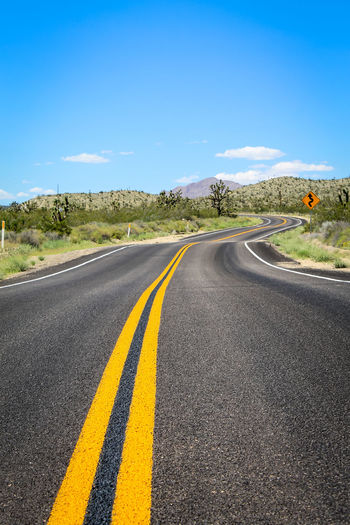 Mojave Desert Road Asphalt Country Country Road Direction Dividing Line Double Yellow Line Joshua Tree Landscape Mojave National Preserve No People Outdoors Road Road Marking Sign The Way Forward Winding Road
