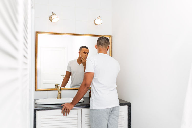 Indoors  Lifestyles Men Skin Care Shaving Morning Clay Mask Bathroom Males  Mirror Looking Reflection Bare Chest Bathrobe Sink Handsome African American Real People Routine Hand Masculinity