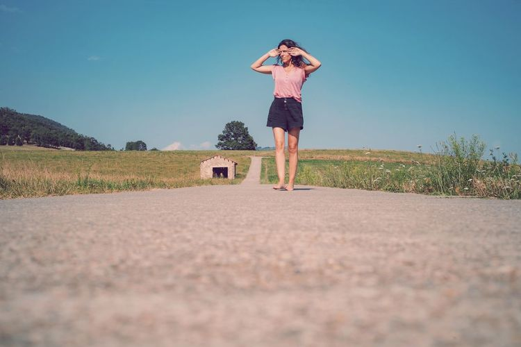 Full length of woman standing on road against sky