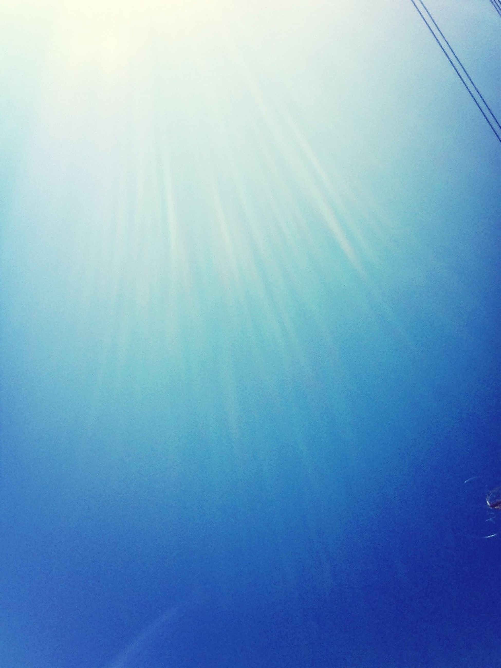 low angle view, blue, clear sky, beauty in nature, tranquility, sun, nature, sunbeam, copy space, sky, scenics, sunlight, tranquil scene, vapor trail, lens flare, day, outdoors, no people, bright, idyllic