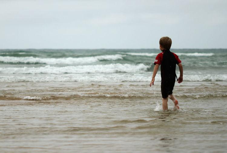 Rear View Of Boy Walking In Sea