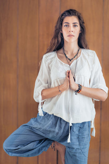Yoga Woman at Home. Tree pose Yoga Woman Tree Pose Vrikshasana Prayer Standing Position Hands Calm White Beautiful Young Relaxation Concetration Exercising Peace Asana Lifestyle Home Studio Wooden Positive Emotion Mindfulness Balance Inner Peace