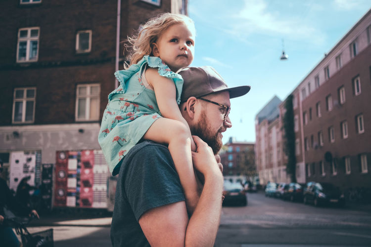 Full length of father and daughter standing on street in city