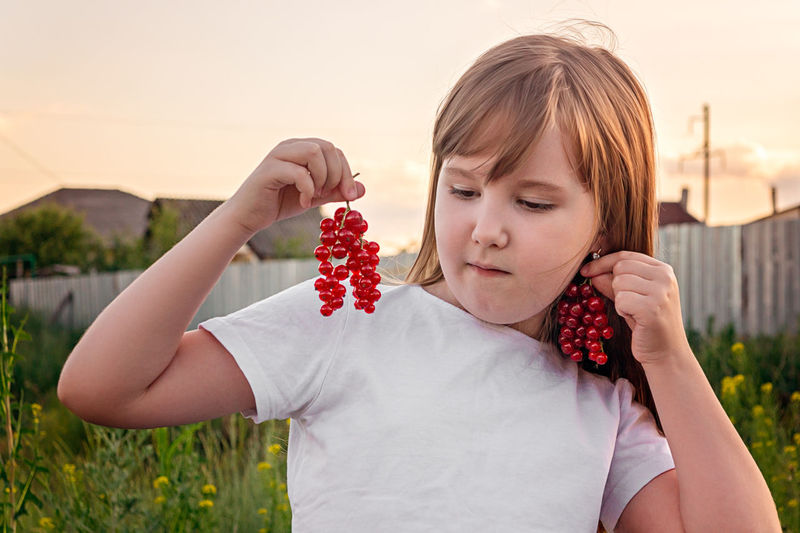Portrait of a pretty girl with earrings of red currant outdoor in summer.