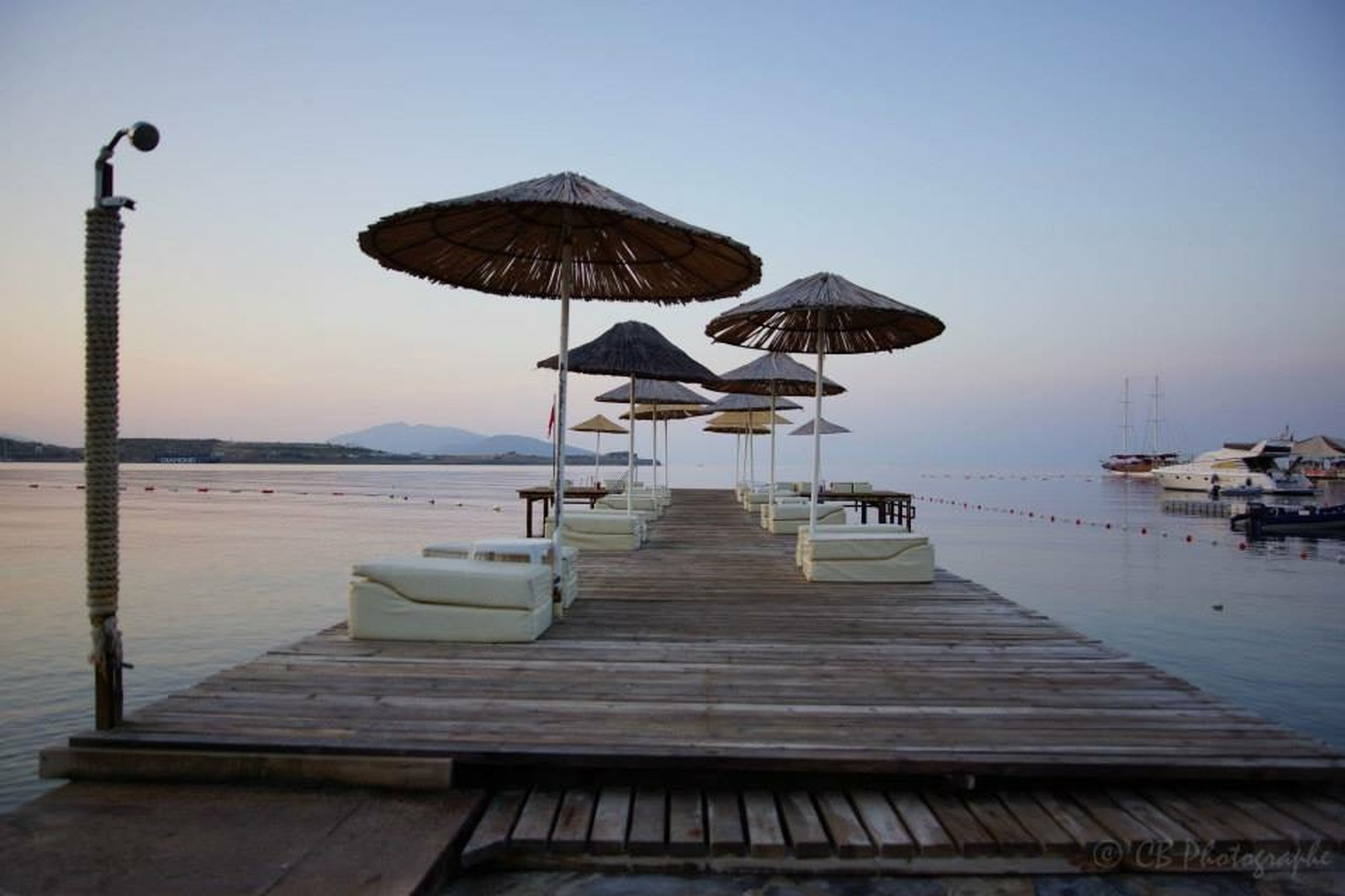 water, clear sky, sea, pier, tranquility, tranquil scene, empty, gazebo, chair, bench, absence, sky, wood - material, moored, scenics, nature, in a row, jetty, outdoors, nautical vessel