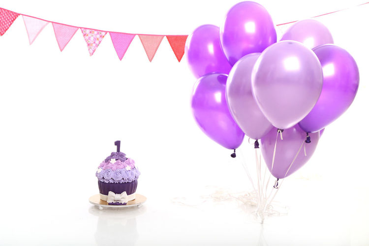 birthday cake and baloons on white background in the studio Baloons Celebration Studio Balloon Banner Birthday Cake Cakesmash Celebration Celebration Event EyeEmNewHere Decoration First Birthday Flags Helium Balloon Indoors Mid-air Multi Colored No People Party - Social Event Purple Purple Flower Studio Shot White Background First Eyeem Photo