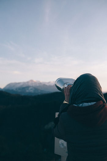 Rear view of woman looking through binoculars during sunset
