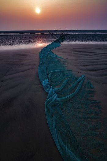 Scenic view of sea against sky at sunset and fishing nets