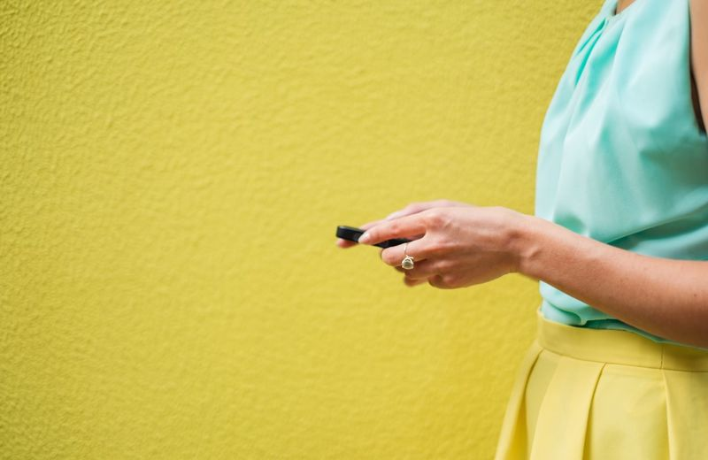 Close-up of woman's hand holding mobile phone
