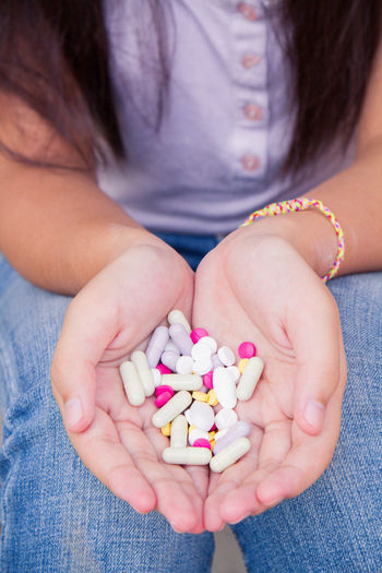 Midsection of woman holding medicines in cupped hands