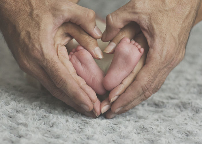 Cropped Hands Of Parents Forming Heart Shape Around Baby Feet
