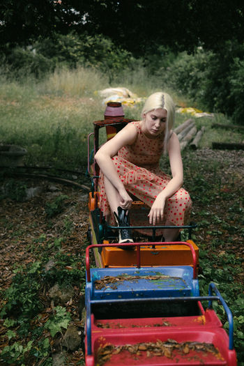 Young Woman Sitting On Miniature Train