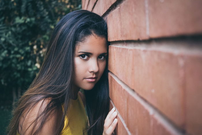 vulnerability Wall Beautiful Woman Brick Defenseless Hair Helpless Long Hair Look Looking At Camera One Person Outdoors Portrait Real People Shyness Standing Teenager Vulnerability  Women Young Adult Young Women The Portraitist - 2018 EyeEm Awards